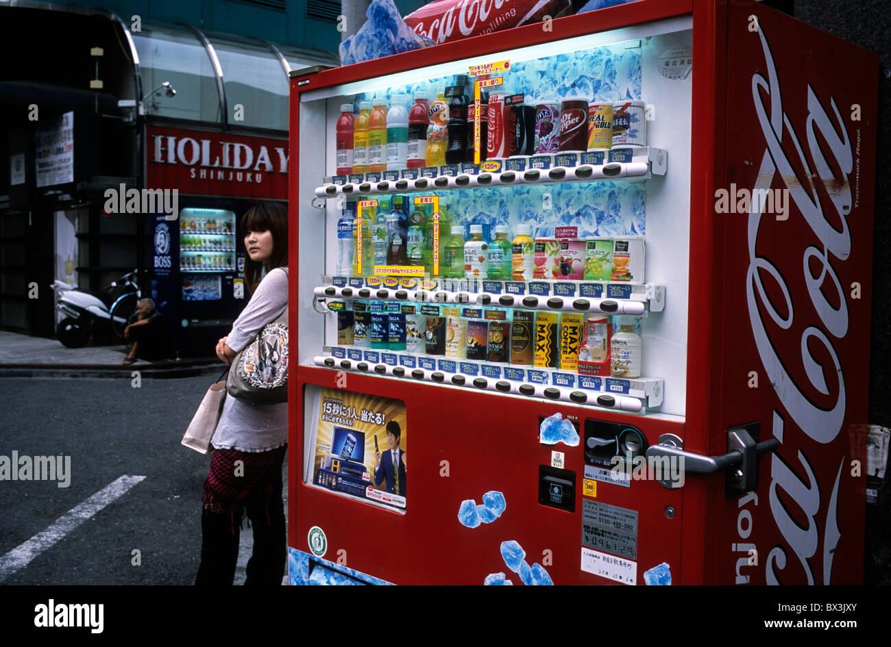 Una señora de pie cerca de una máquina expendedora de bebidas automático en Shinjuku, Tokio, Japón. Imagen De Stock