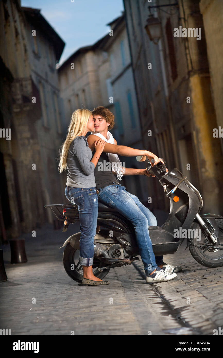 Pareja joven beso en scooter en calle Imagen De Stock