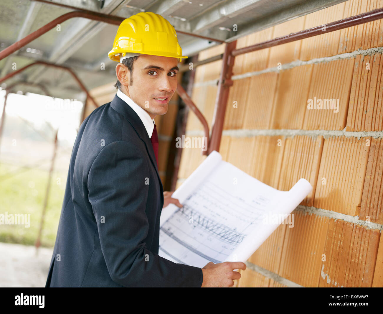Arquitecto con blueprint en sitio en construcción Imagen De Stock