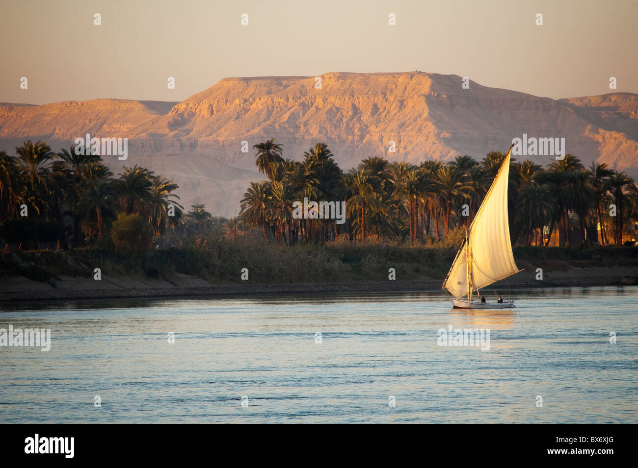 Una impresionante y bella imagen de un velero tradicional egipcio llamado faluca por el Nilo al atardecer, con las Imagen De Stock