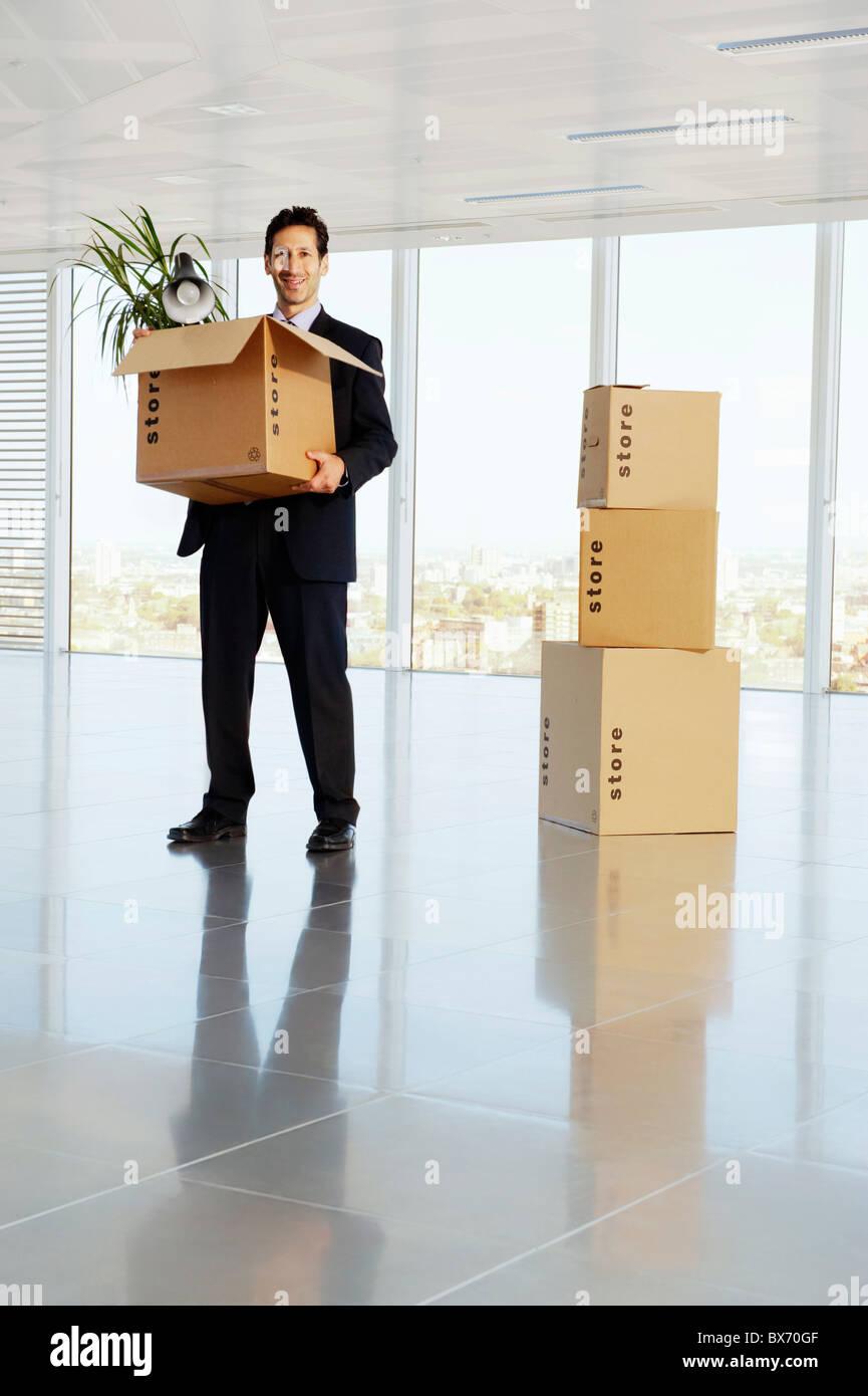 El hombre de negocios feliz celebración caja de cartón con sus pertenencias en espacio de oficinas vacío Foto de stock