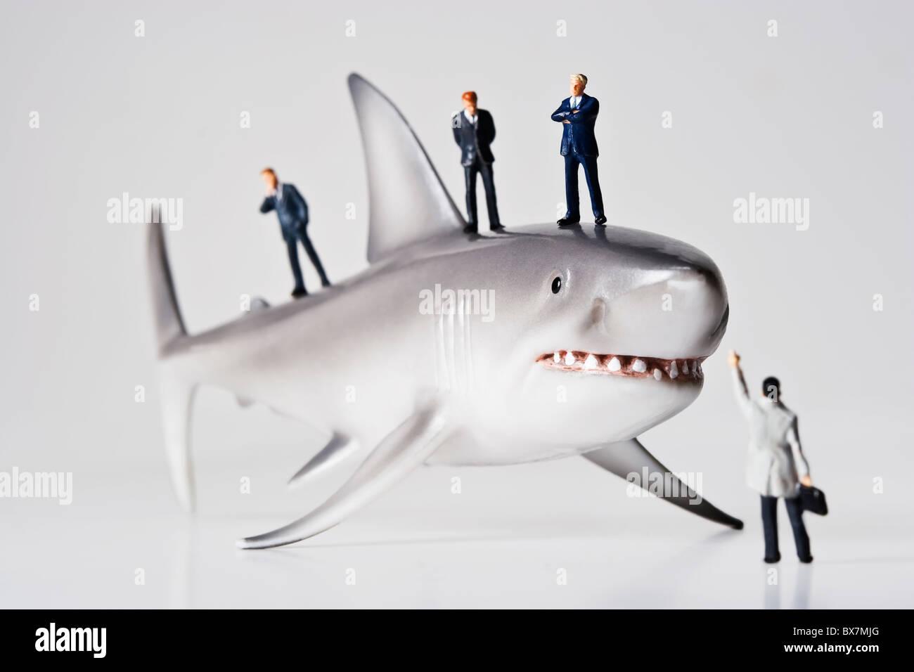 Figurines de negocios colocados con un tiburón figurilla. Imagen De Stock