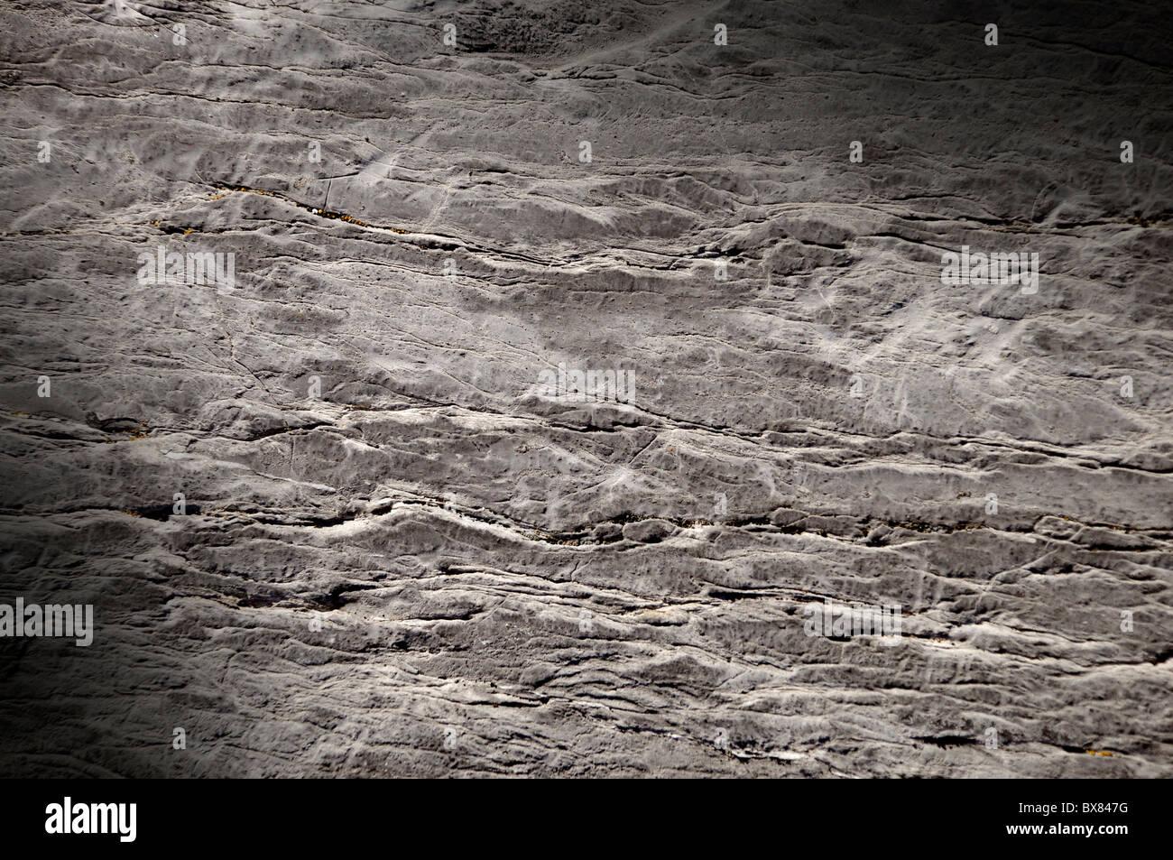 Roca agrietada la textura de la superficie iluminada en diagonal. Imagen De Stock