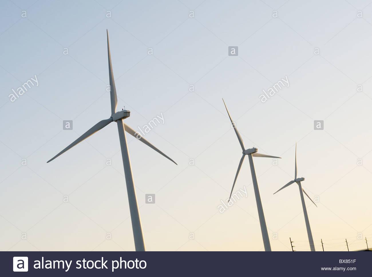 Tres turbinas eólicas con líneas de transmisión eléctrica en el fondo, al amanecer Imagen De Stock