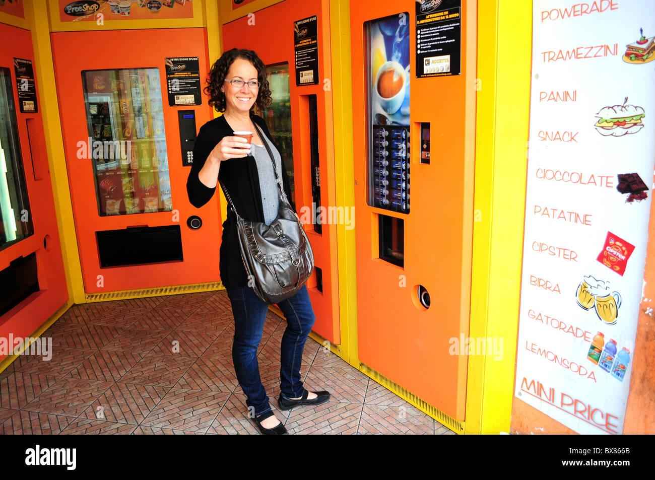 Chica bebiendo café desde una máquina en Roma Italia Imagen De Stock