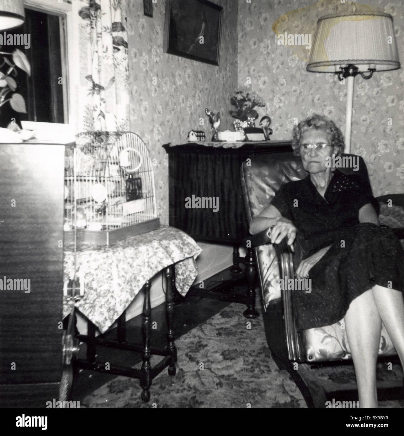 Anciana mirando las aves de jaula vacía. Envejecimiento femenino Casa Americana en blanco y negro 1950 Imagen De Stock