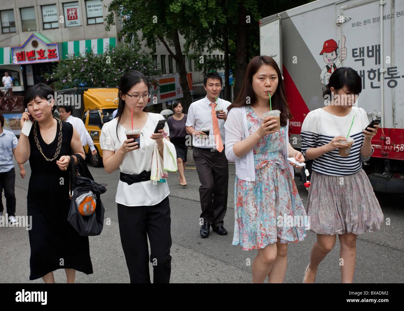 Los trabajadores de la oficina de Seúl usando sus teléfonos móviles a la hora del almuerzo, Corea Imagen De Stock