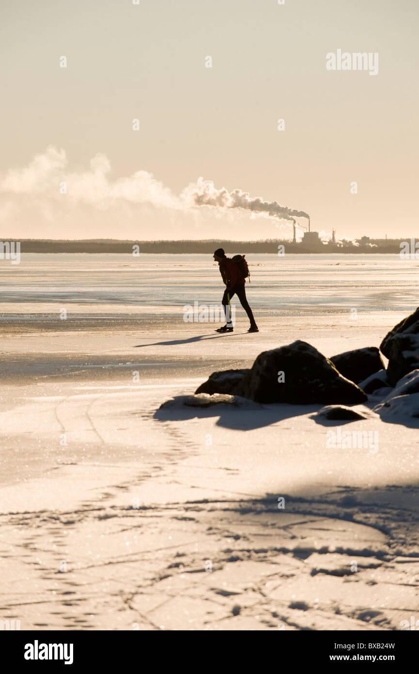 Silueta de hombre patinando en el lago congelado, la fábrica en segundo plano. Imagen De Stock