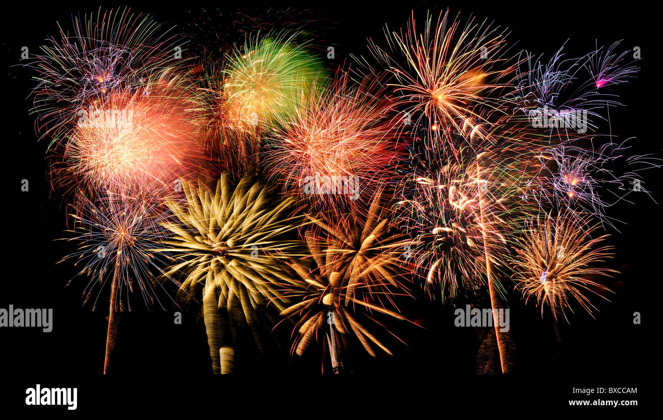 Brillantes y coloridos fuegos artificiales contra un cielo nocturno negro Foto de stock