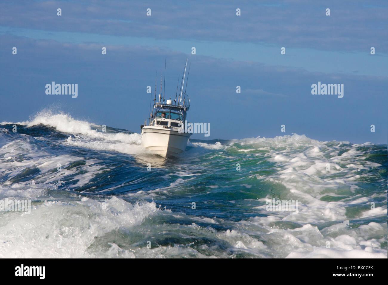 Embarcaciones de recreo Pesca Deportiva estilo barco navegando por el mar embravecido, cresterías una gran ola acercándose a la cámara en una mañana brillante. Foto de stock
