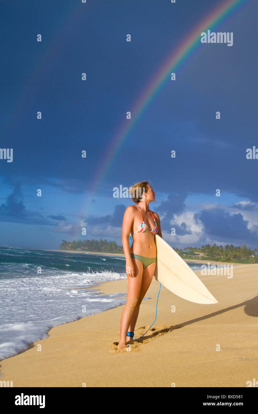 Un impresionante arco iris sobre Rocky Point, como un surfista chica camina por la playa, en la costa norte de Oahu, Imagen De Stock