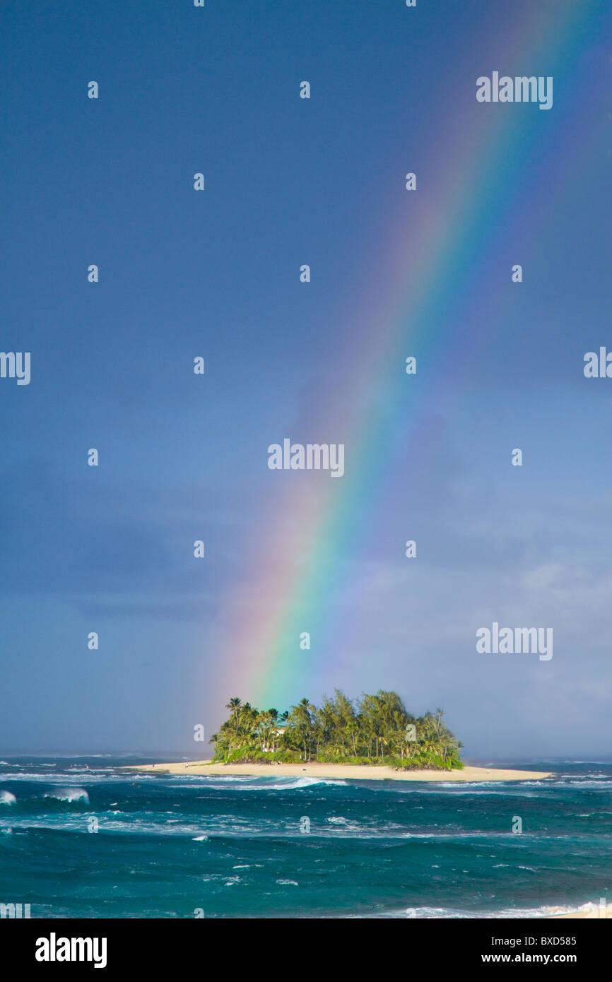 Un arco iris de colores brillante cayendo sobre una pequeña isla desierta. Imagen De Stock