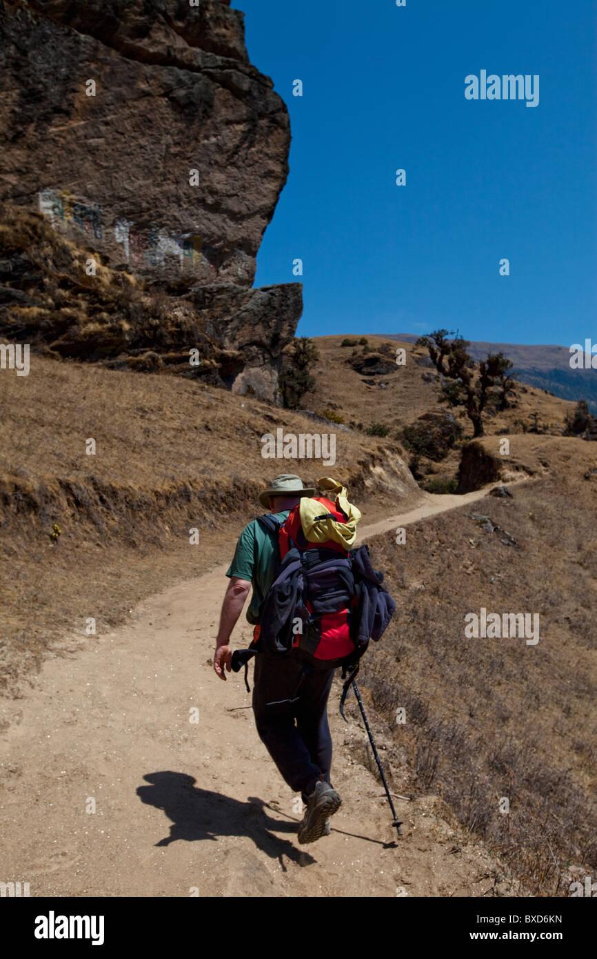 Un caminante sigue un sendero de comercio más allá de un acantilado de roca decoradas con budistas script. Imagen De Stock