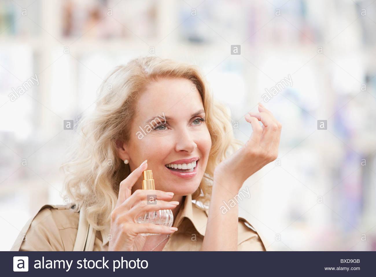 Mujer sonriente probando el perfume en la tienda Imagen De Stock