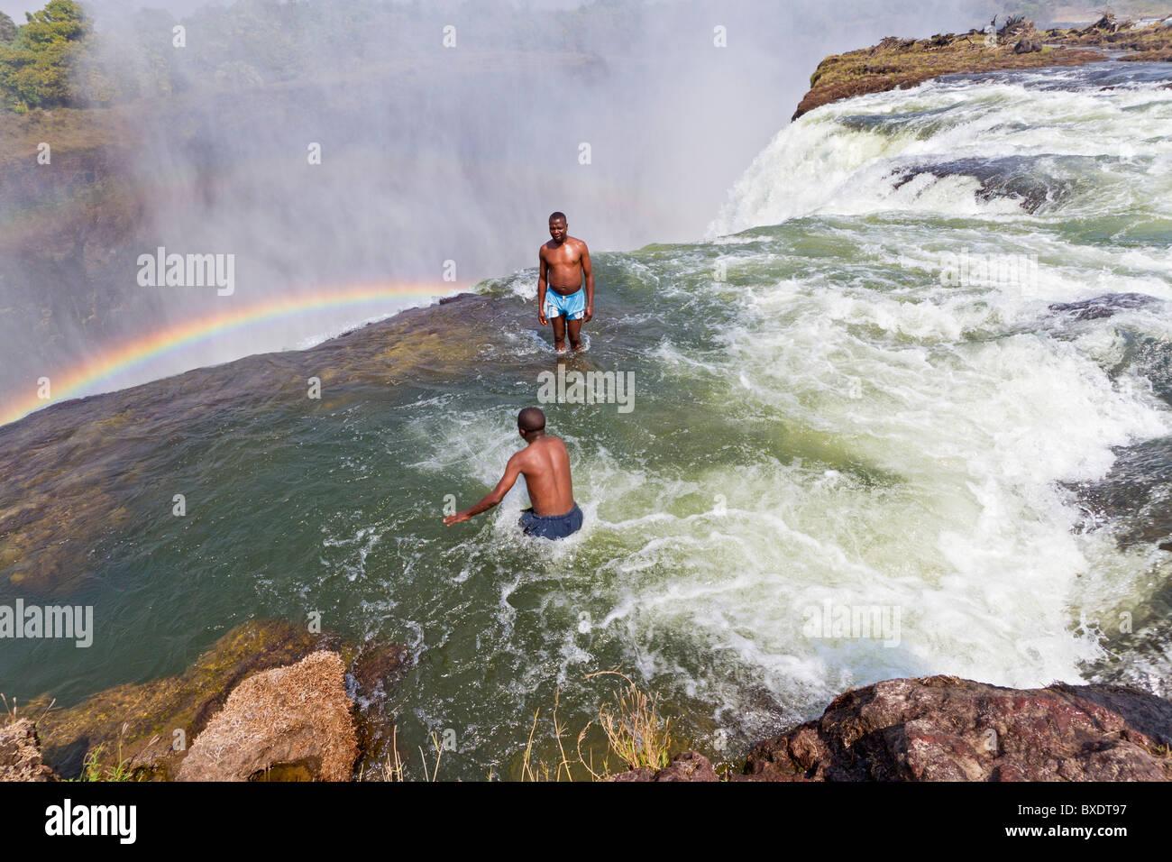 El hombre salta a la piscina del diablo en las Cataratas Victoria. Imagen De Stock