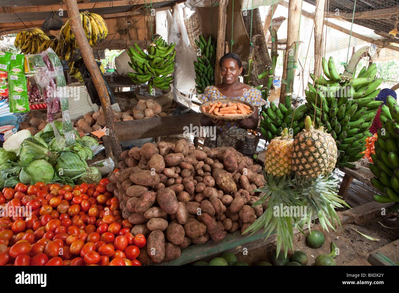 Una mujer sostiene una cesta de verduras frescas en el mercado en Dodoma, Tanzania, África Oriental. Imagen De Stock