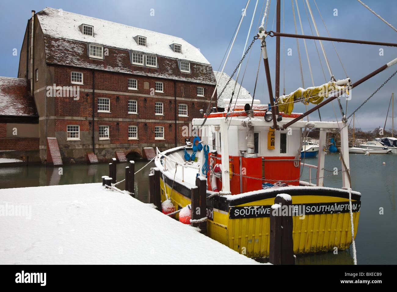 La nieve cubrió la pesca de arrastre de shell comerciales amarillos amarrados junto al muelle en el molino de agua Ashlett Southampton Foto de stock