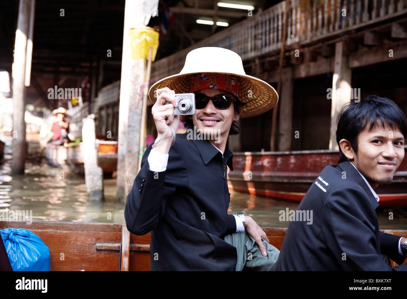 Los turistas en sombreros de paja tradicionales cabalgando por el mercado  flotante Damnoen Saduak en un a929d1f26d3
