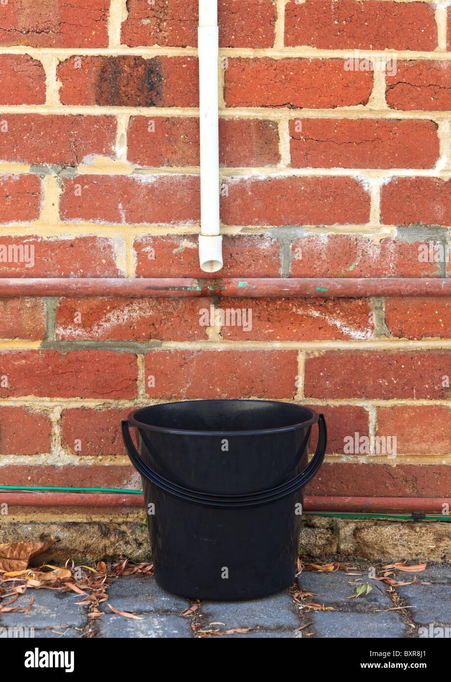 Un balde para recoger el agua para su reutilización debajo de un tubo de salida del aire acondicionado. Imagen De Stock