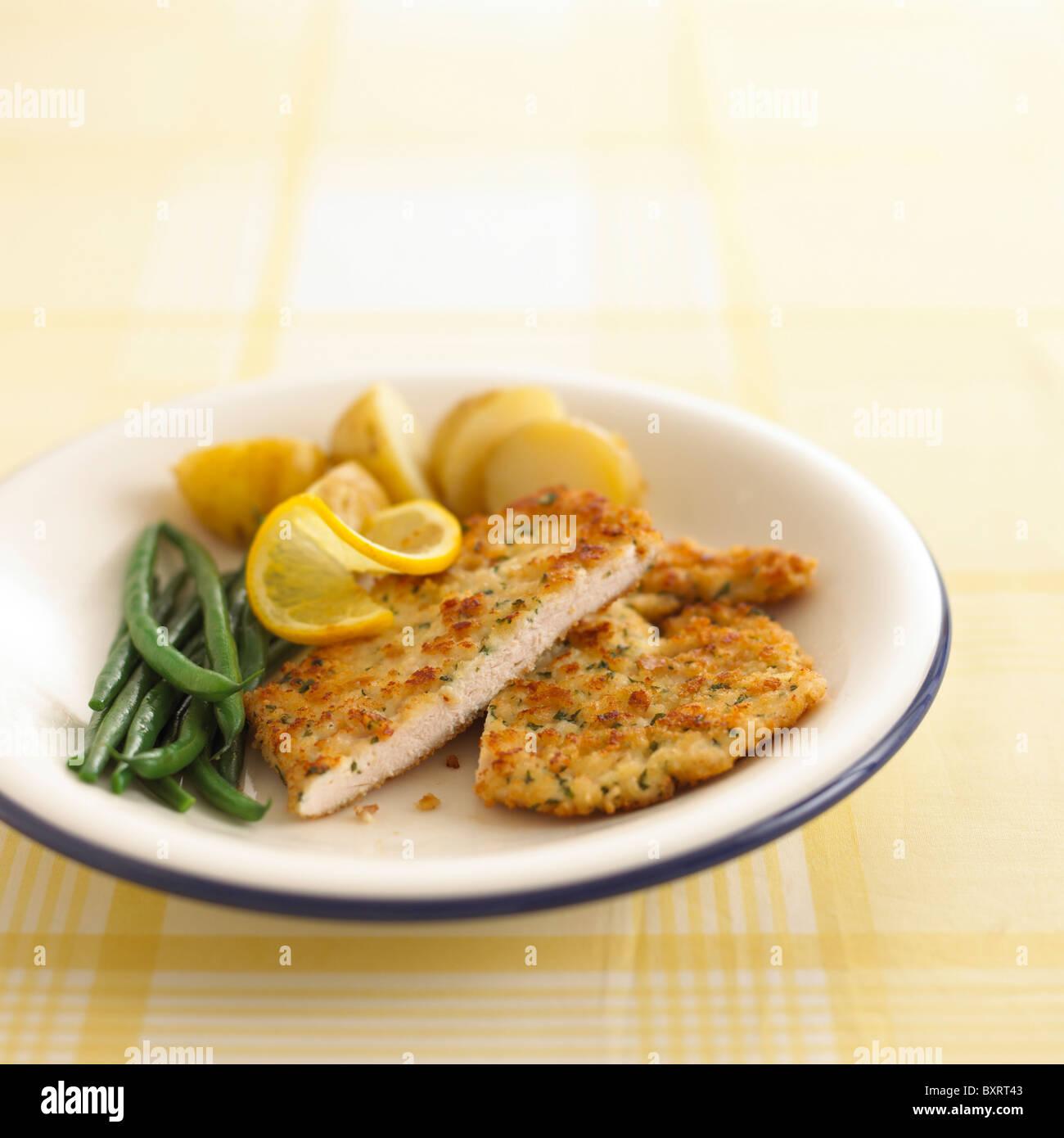 Escalope de pollo, judías verdes y patatas nuevas en la placa blanca. Imagen De Stock