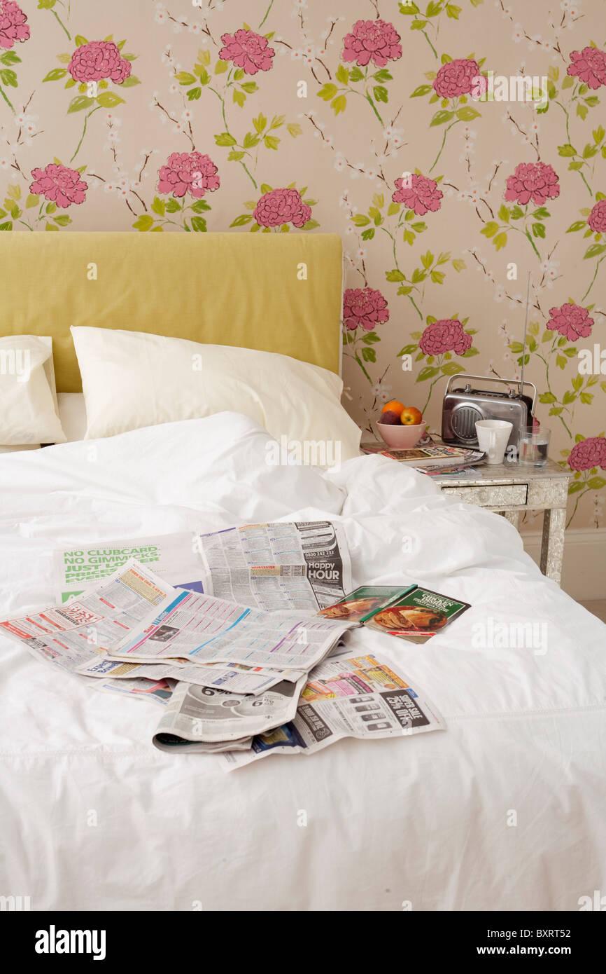 Cama desordenada con cubiertas en periódicos Imagen De Stock