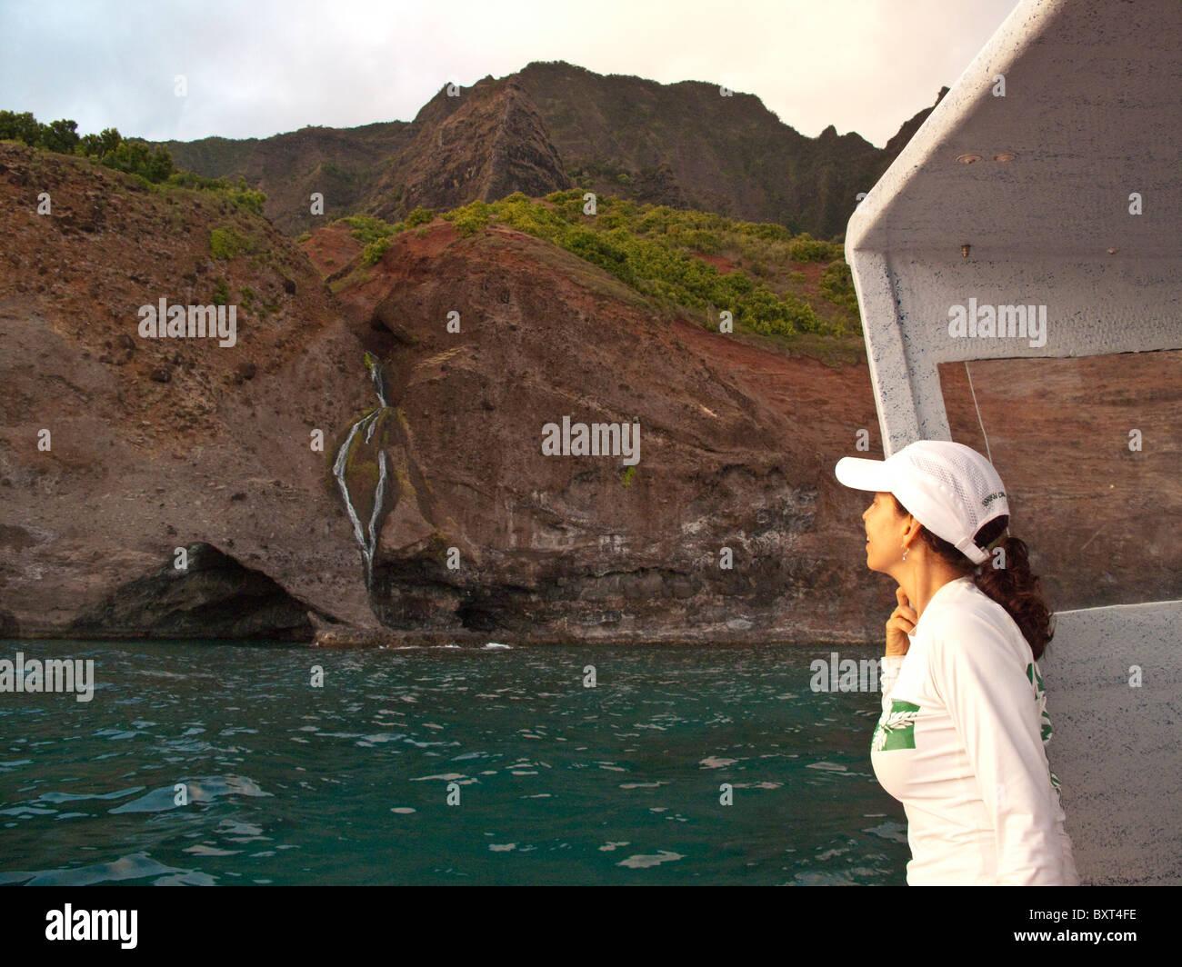 Foto de mujer madura buscando en cascada en la costa Na Pali de Kauai, tomada desde el agua en las primeras horas de la mañana la luz Foto de stock