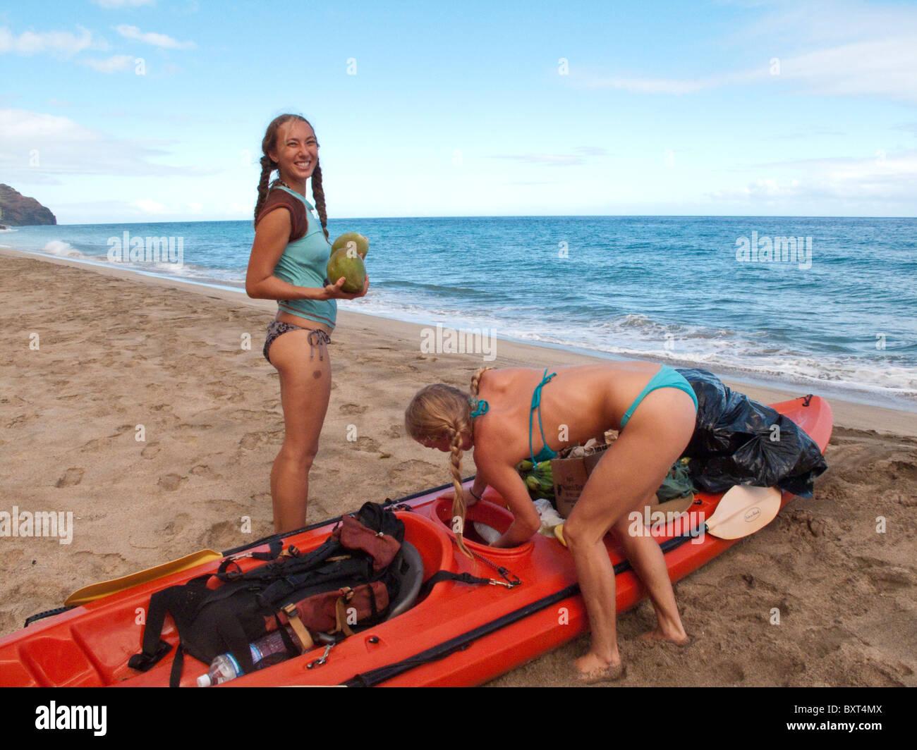 Después de kayak desde Haena, dos mujeres jóvenes preparándose para comer cocos en Kalalau beach a lo largo de la costa de Na Pali, Kauai Foto de stock