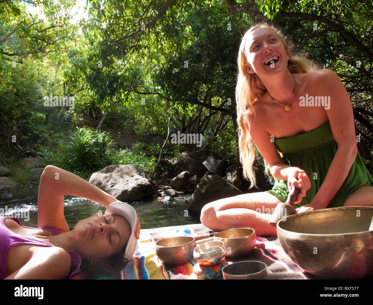 Dos mujeres descansando sobre una gran roca en el Valle Kalalau, mientras escucha el canto cuencos tibetanos para la curación, la costa de Na Pali, Kauai Foto de stock