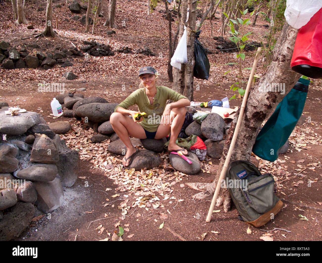 Mujer joven sentada sobre una roca y comiendo un mango en un camping en Valle Kalalau, Costa Na Pali, Kauai Foto de stock