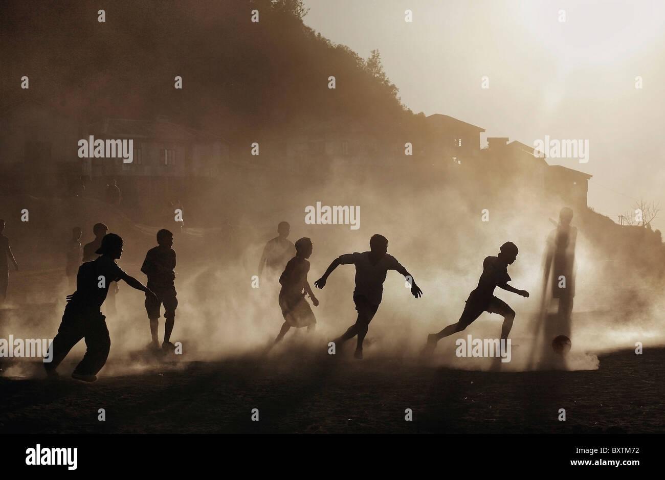 Siluetas de Mizo niños corriendo en un polvoriento campo de Fútbol al Atardecer Imagen De Stock