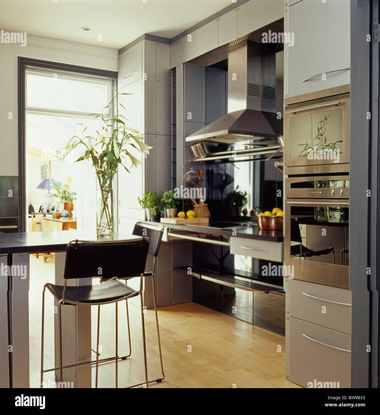 Cuero negro y taburetes de acero en barra para desayunar en casa cocina moderna con pisos de - Taburetes para barra de cocina ...