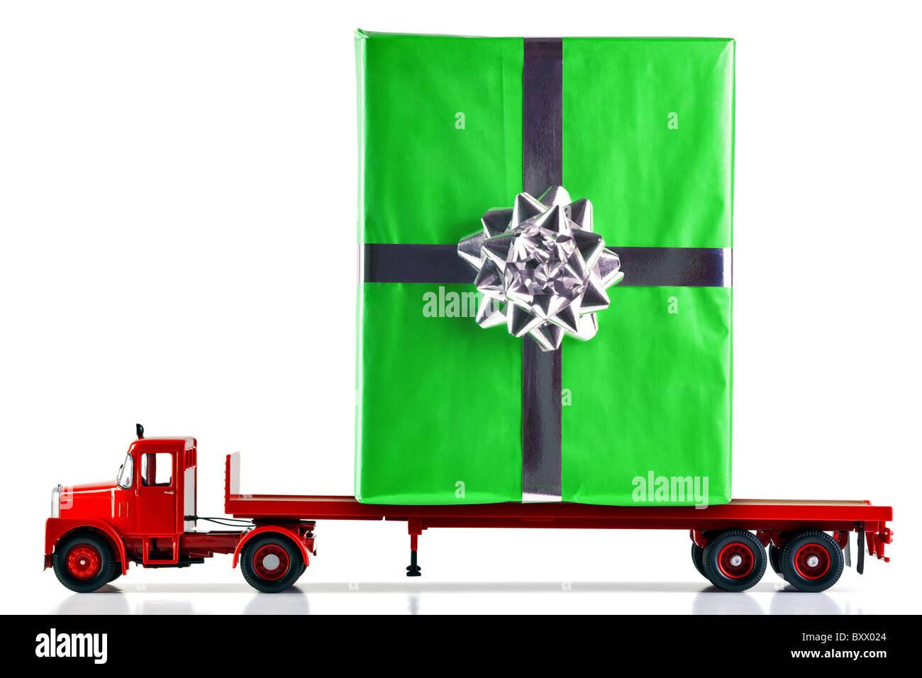 Un envoltorio de regalo presente se entregue en un camión de plataforma plana. Aislado sobre un fondo blanco. Imagen De Stock