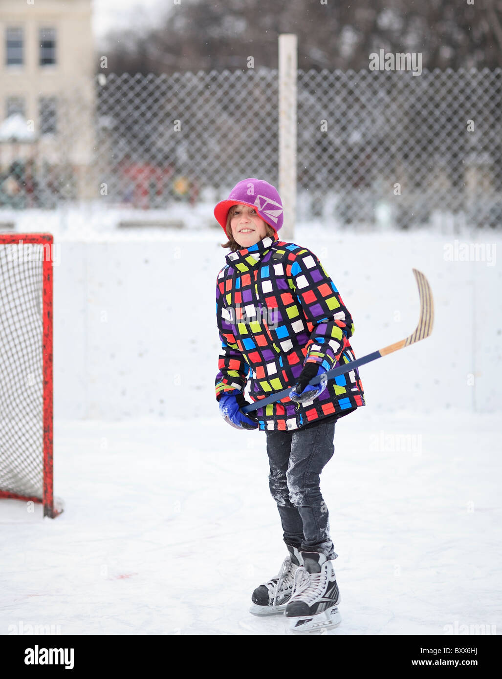 Joven jugador de hockey sobre hielo en una pista de patinaje al aire libre. Winnipeg, Manitoba, Canadá. Imagen De Stock