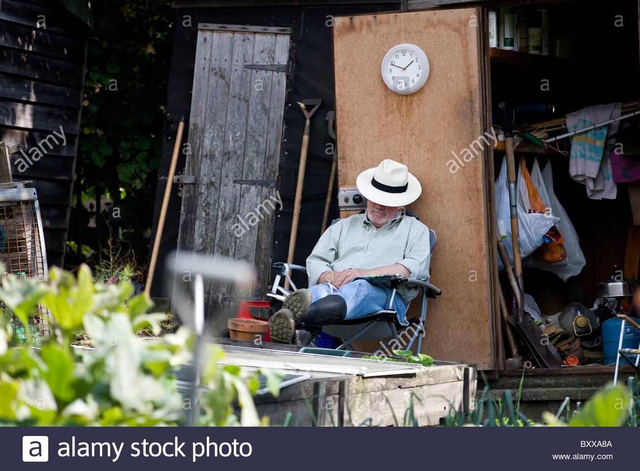 Un anciano hombre descansando sobre una asignación Imagen De Stock