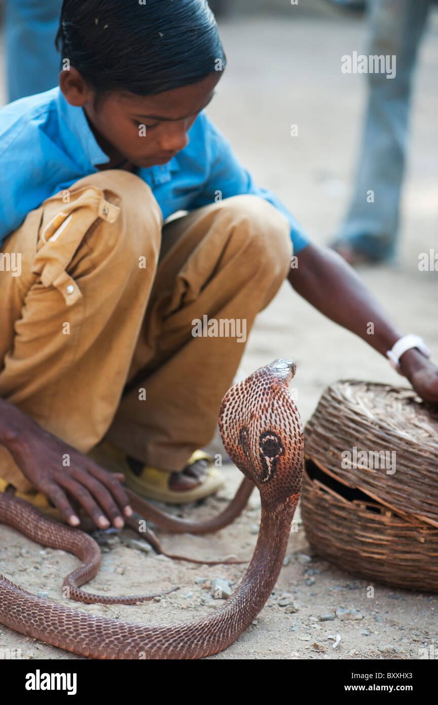 Pobre niño indio de castas inferiores la mendicidad con babas Cobra en una calle de la India. En Andhra Pradesh, Foto de stock