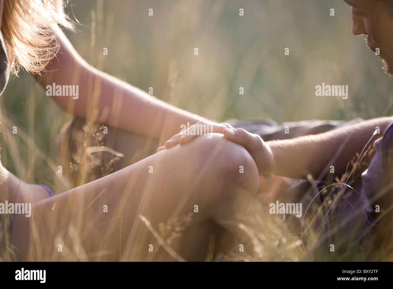 Detalle de una pareja joven afuera, mans mano sobre la rodilla de los womans Foto de stock