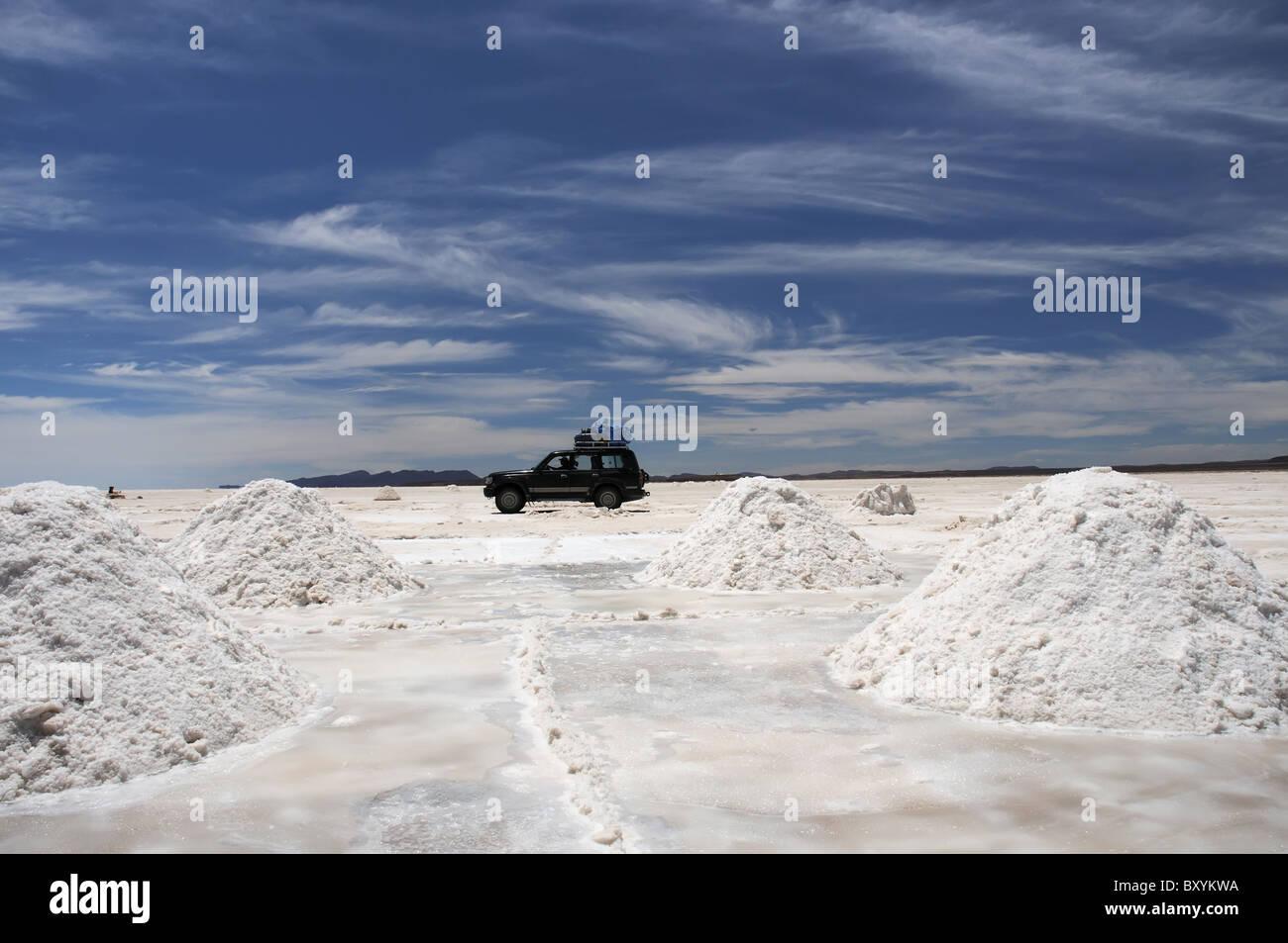 Un vehículo cruzando el salar de Uyuni entre montones de sal excavado y preparado para la purificación Imagen De Stock