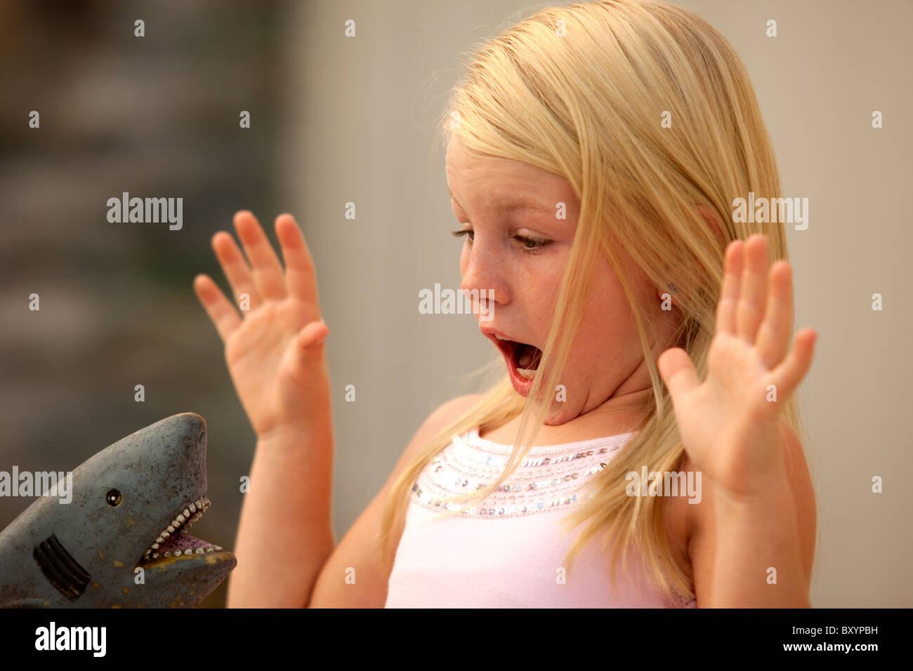 Niña miedo de shark toy Foto de stock