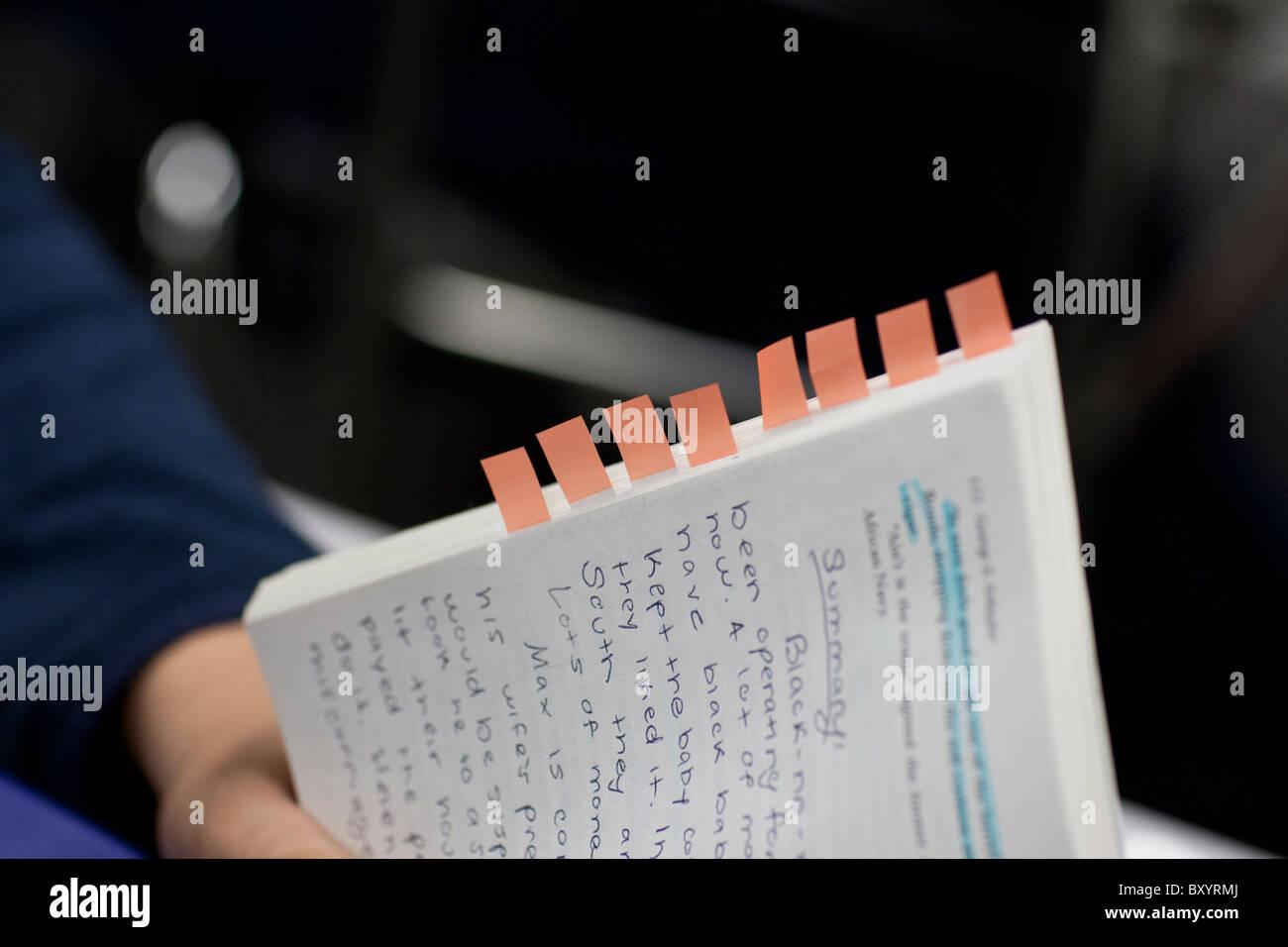 Estudiante posee copia de novela con texto resaltado, notas manuscritas y marcadores de tabulación de anotación Imagen De Stock