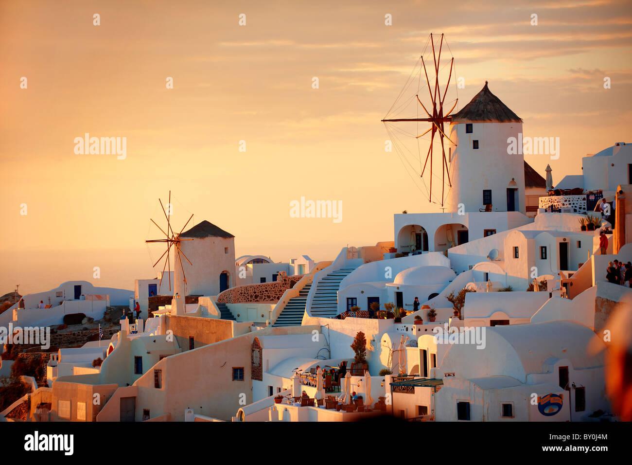 Oia (Ia) Santorini - Molinos de viento y la ciudad al atardecer, de las islas Cícladas griegas - fotos, dibujos Imagen De Stock