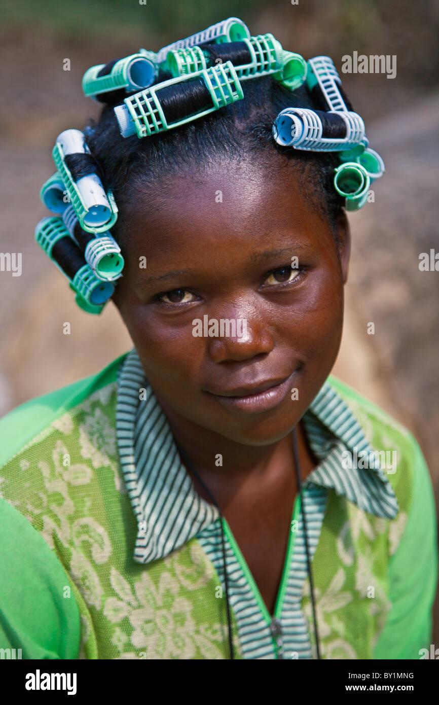 Una bonita muchacha con rulos que coincidan con los colores de su vestido. Imagen De Stock