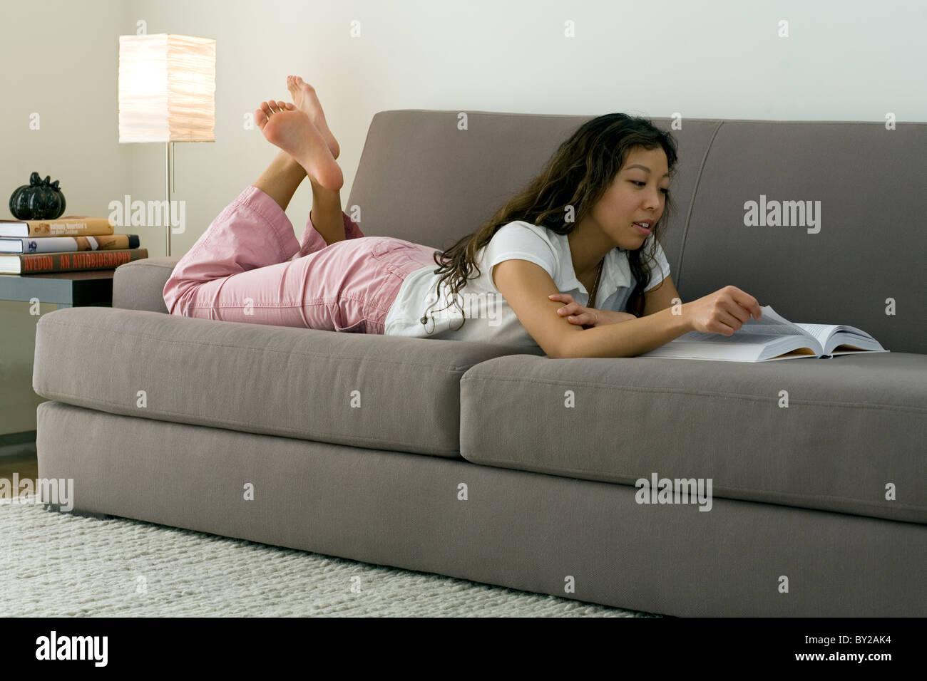 Una mujer joven la lectura en su sofá en casa. Foto de stock