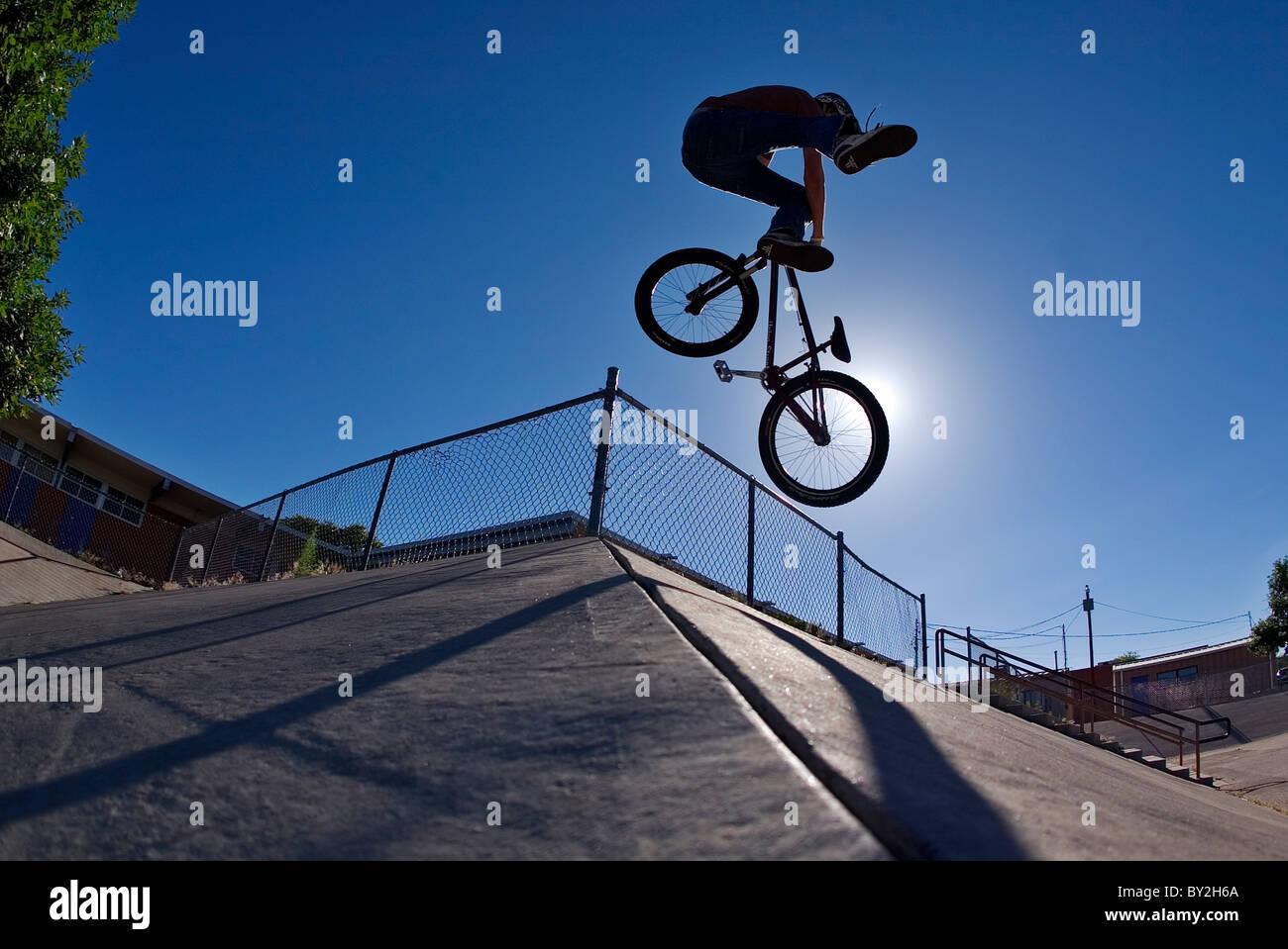 Un ciclista de montaña hace un tailwhip sobre un banco de hormigón en Albuquerque, NM. Imagen De Stock