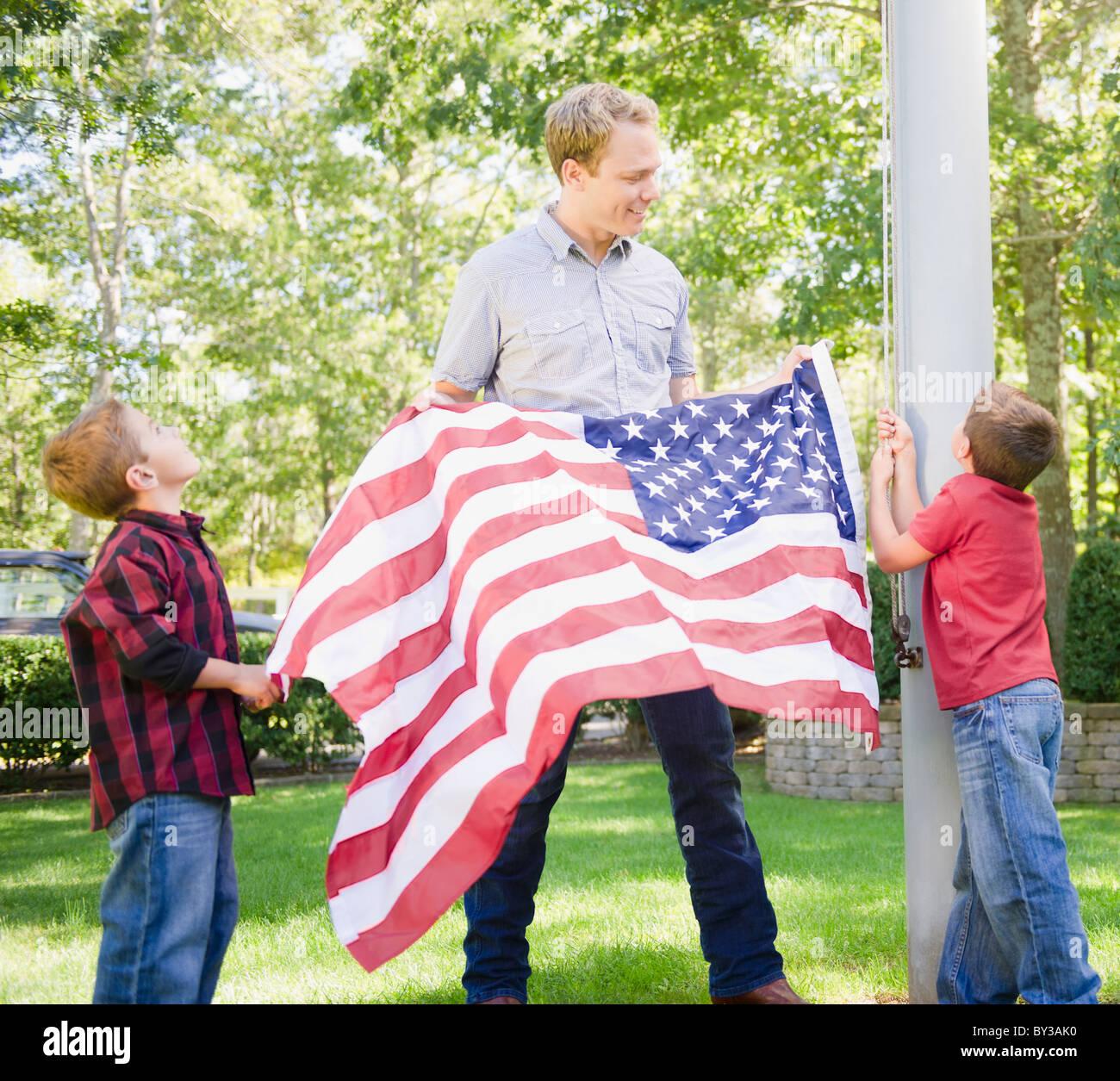 Los Estados Unidos, Nueva York, Flandes, padre con dos niños (4-5, 8-9) colgando de la bandera americana en Imagen De Stock