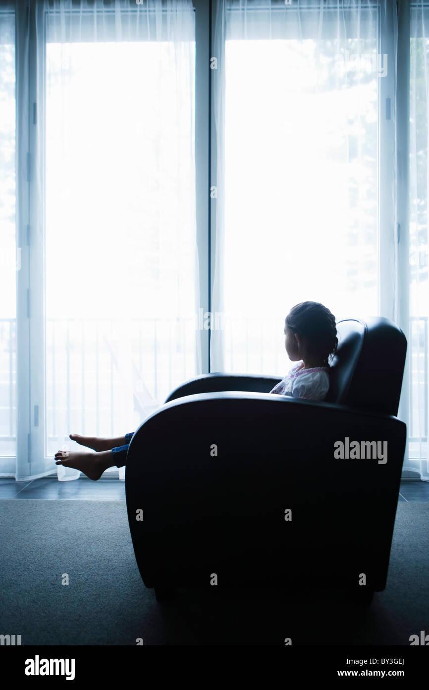 Niña de seis años se sienta en estilo art deco sillón junto a la ventana. Imagen De Stock