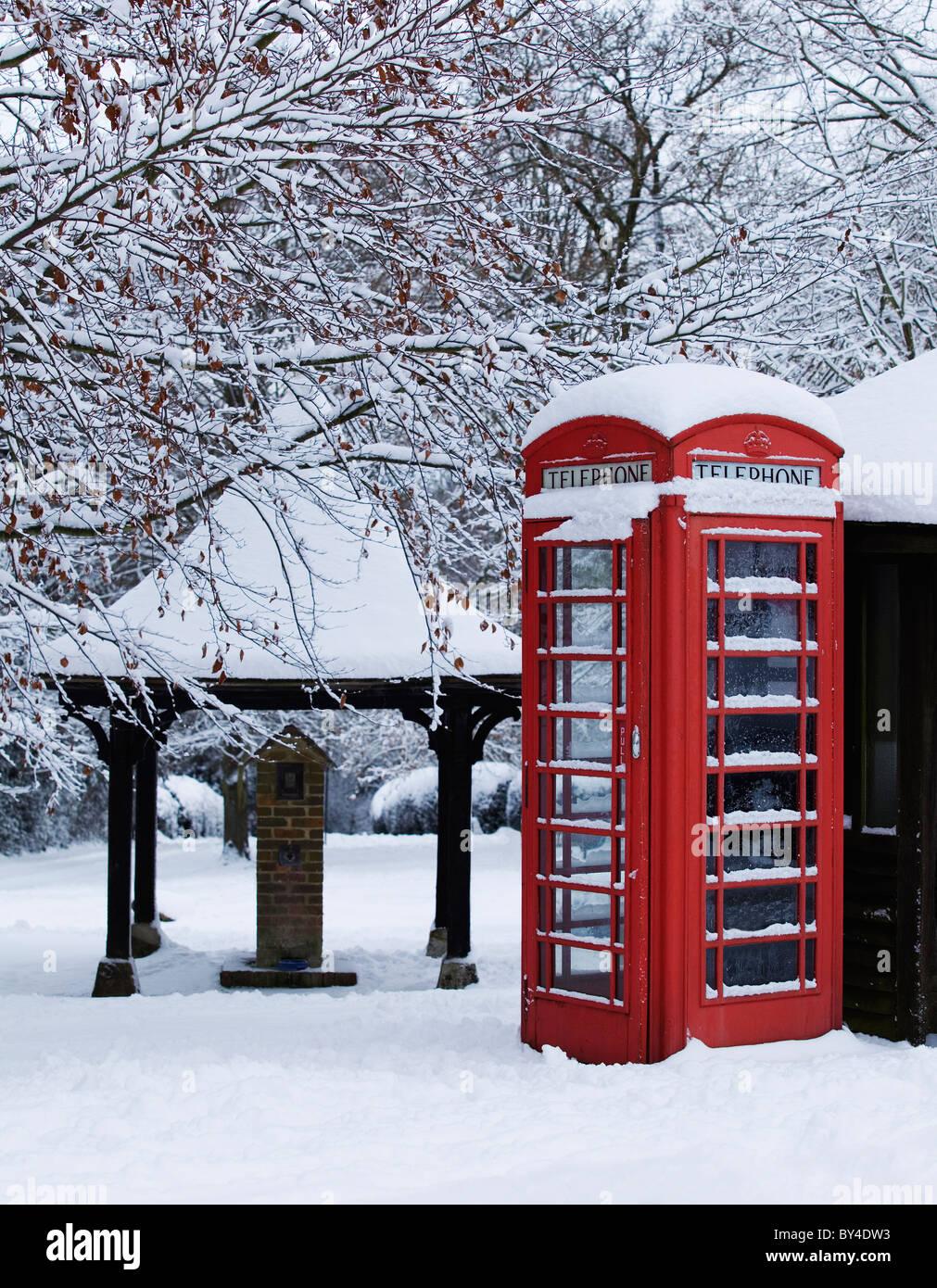 Teléfono rojo tradicional caja con nieve en una aldea inglesa verde Imagen De Stock