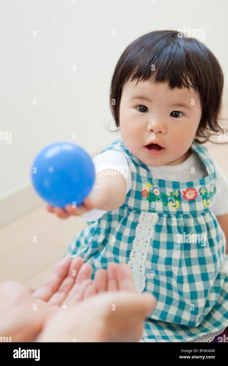 Chica dando bola a la madre Foto de stock