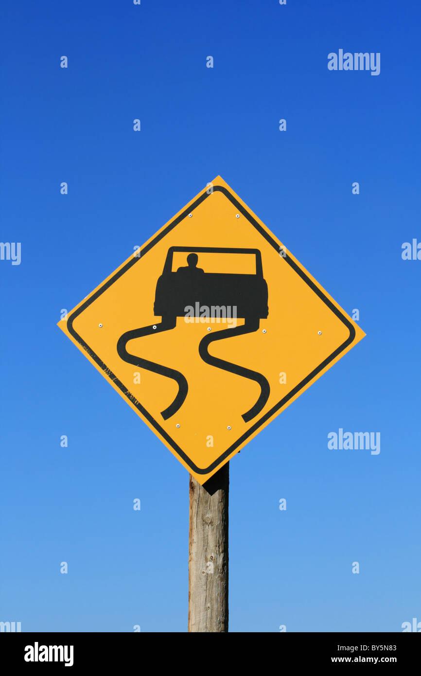 Señal de Carretera resbaladiza con coche y patinar marcas en negro sobre amarillo con fondo de cielo azul Imagen De Stock