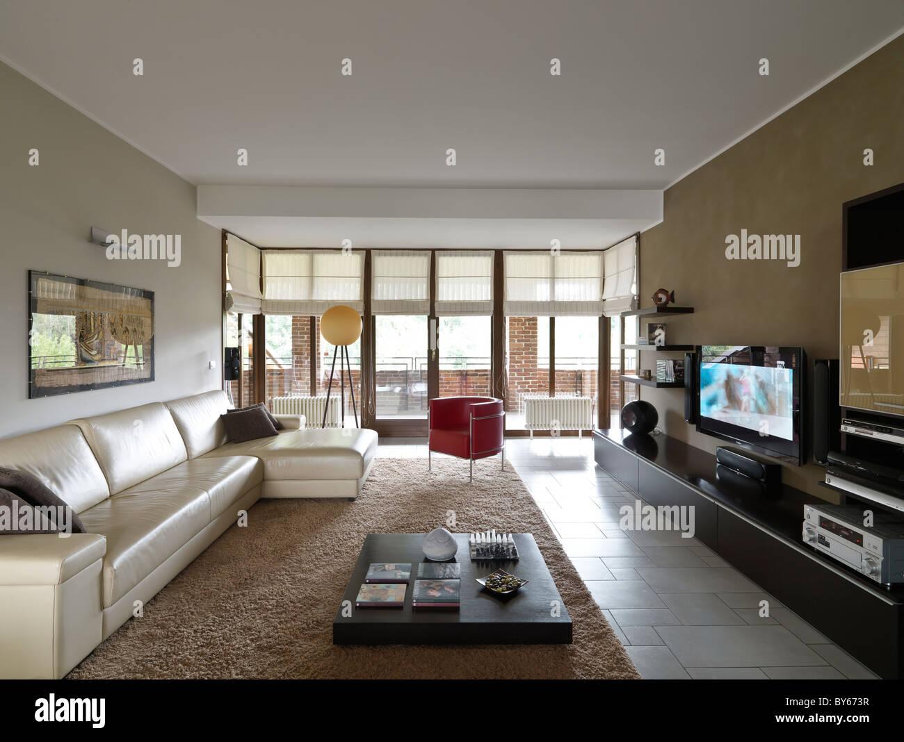Moderna sala de estar con un sofá contemporáneo y un sillón de cuero de color beige y rojo Imagen De Stock
