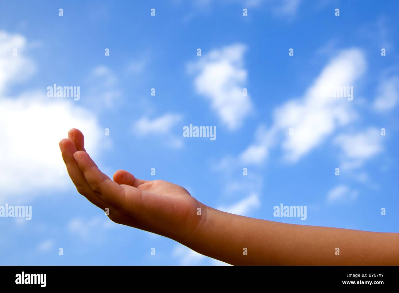 Abrir la mano de un niño contra Un nublado cielo azul Foto de stock